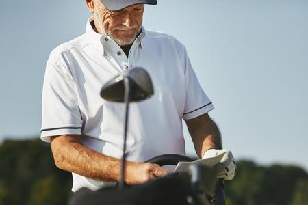 Sporty senior man reading his scorecard while enjoying a round of golf on a sunny day 写真素材