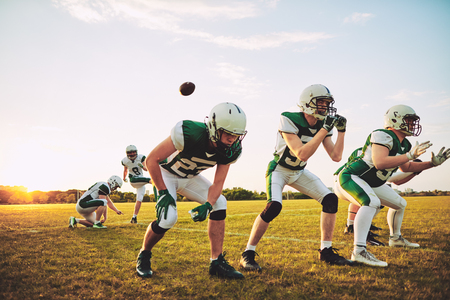 Group of young American football players practicing place kicking together on a football field during a late afternoon practice Stock Photo