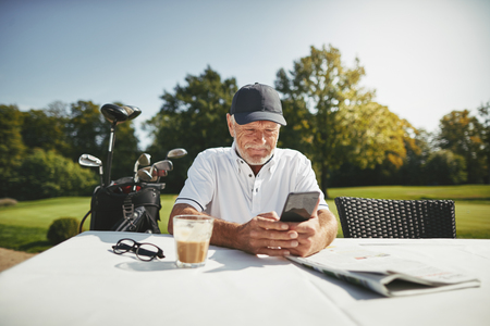 Smiling senior man reading a text message and drinking a coffee while relaxing at a course restaurant after a playing round of golf
