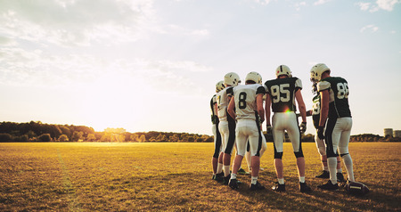 Group of young American football players standing in a circle talking strategy together during an afternoon practice Stock Photo