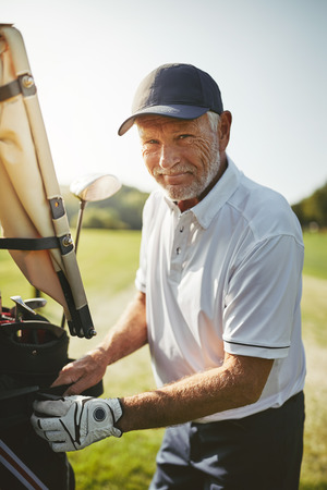 Smiling senior man putting his bag full of clubs on a cart while enjoying a round of golf on a sunny day Stock Photo