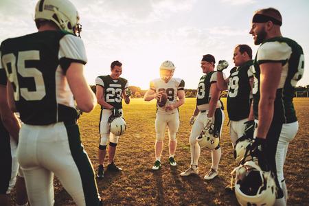 Joven mariscal de campo de fútbol americano discutiendo jugadas ofensivas con sus compañeros de equipo durante una sesión de práctica al aire libre en un campo deportivo por la tarde