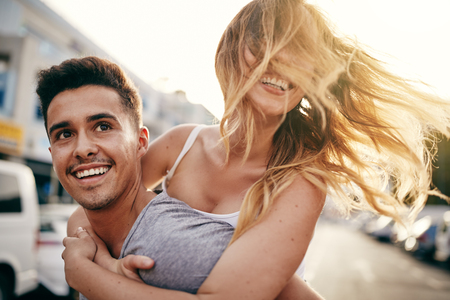 Laughing young woman being piggybacked by her boyfriend while enjoying a day together in the city