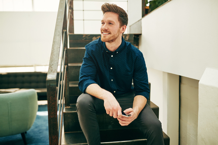 Smiling young businessman with a beard sitting alone on stairs during his break in a modern office holding a cellphone