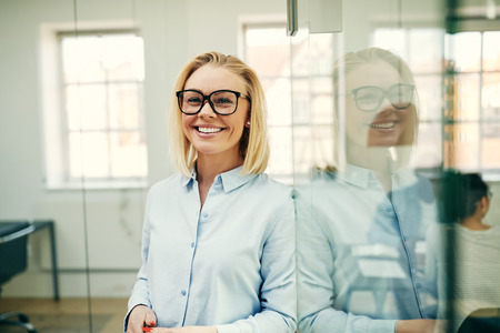 Young businesswoman smiling confidently while leaning against a glass wall in an office with colleagues in the background