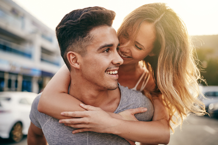 Smiling young man giving his laughing girlfriend a piggyback while walking together down a street in the city Stock Photo
