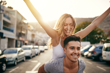 Laughing young woman with her arms raised being being carried on her boyfriends shoulders while having fun together in the city