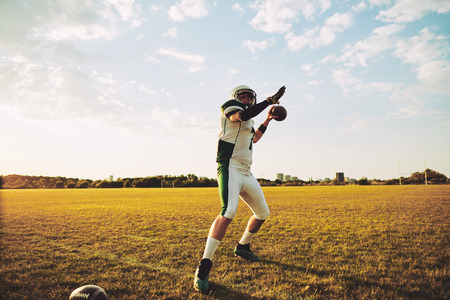 American football quarterback about to throw a football during team practice drills on a sports field in the afternoon Stock Photo