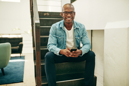 Smiling young African businessman wearing glasses sitting on stairs in an office reading text messages on a cellphone