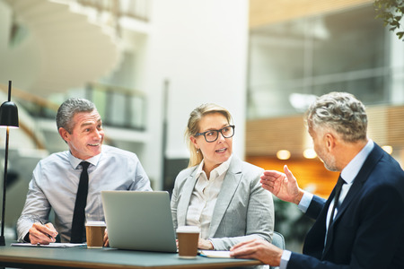 Three mature business colleagues discussing work together while having a meeting at a table in the lobby of a modern office building Stock Photo