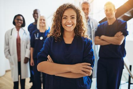 Junge Ärztin, die lächelt, während sie in einem Krankenhausflur mit einer vielfältigen Gruppe von Mitarbeitern im Hintergrund steht