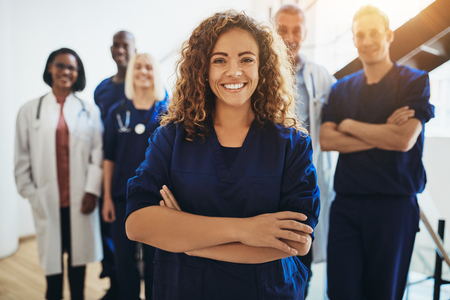 Young female doctor smiling while standing in a hospital corridor with a diverse group of staff in the background Stock Photo - 110544104