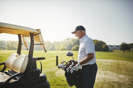 Senior man putting his bag full of clubs on a cart while enjoying a round of golf on a sunny day