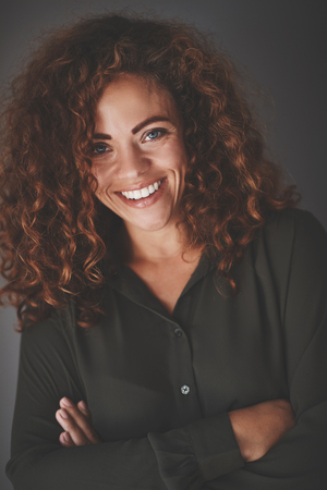 Confident young businesswoman with long curly hair smiling while standing with her arms crossed against a gray background