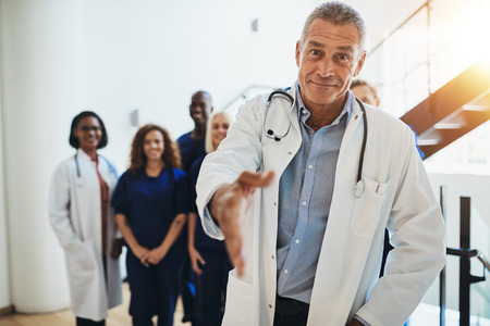 Smiling mature male doctor extending a welcoming handshake while standing in a hospital corridor with his diverse staff standing behind him