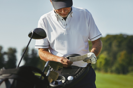Sporty senior man looking at his scorecard while enjoying a round of golf on a sunny day