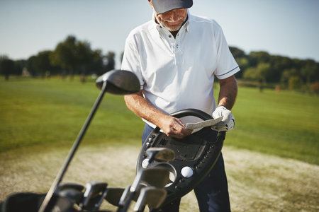 Sporty senior man standing by his clubs and reading his scorecard while enjoying a round of golf on a sunny day 写真素材