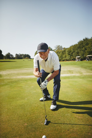 Sporty senior man standing on a green planning his putt while playing a round of golf on a sunny day Stock Photo