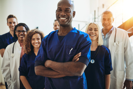 Young African male doctor smiling while standing in a hospital corridor with a diverse group of staff in the background Imagens