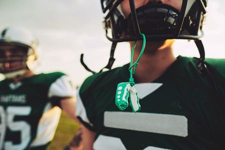 Closeup of a young American football player with his mouthguard hanging from his helmet during an afternoon practice 免版税图像