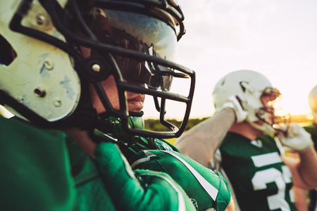 Closeup of a young American football player wearing a helmet and visor standing with his teammates during a practice session