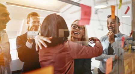 Twee lachende jonge zakenvrouwen knuffelen tijdens het brainstormen met plaknotities op een glazen wand met collega's in een modern kantoor Stockfoto