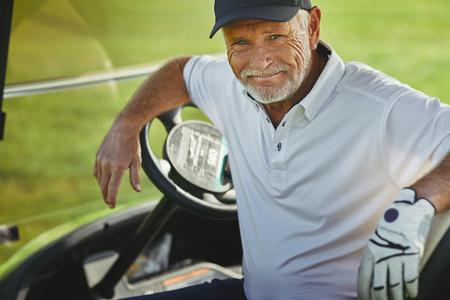 Glimlachende senior man zit in een kar terwijl hij geniet van een rondje golf op een zonnige dag