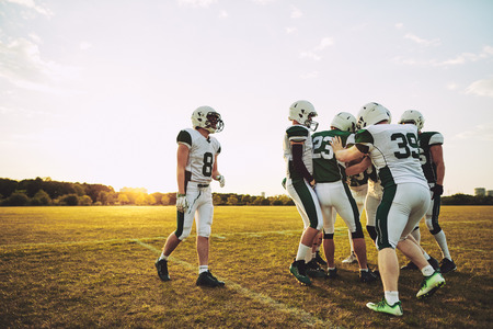 Team of young American football players having fun together on a sports field during an afternoon practice session Stock Photo - 118127200