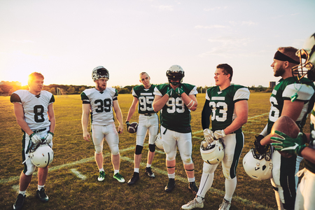 Group of young American football players talking together while standing on a sports field during a late afternoon practice Stock Photo - 114419348
