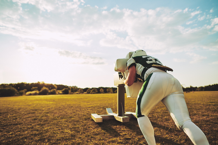 American football player practicing tackling with a tackle sled outside on a sports field in the late afternoon