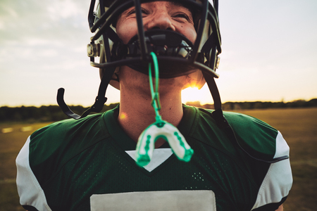 Closeup of a young American football player with his mouthguard hanging from his helmet during a team practice session Stock Photo