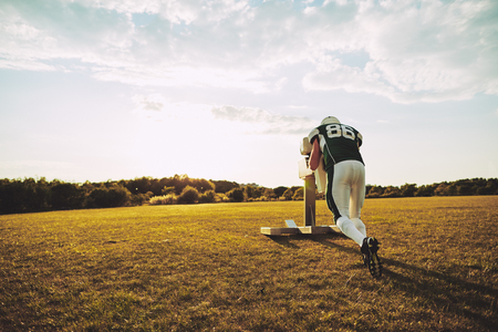 American football player doing tackle drills with a tackle sled outside on a sports field during an afternoon practice Stock Photo