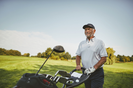 Smiling senior man walking along a fairway with his club bag while playing a round of golf on a sunny day