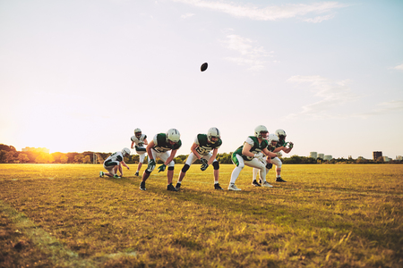 Young American football team doing place kicking drills together on a sports field during an afternoon practice