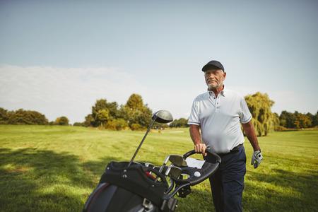 Lächelnder älterer Mann, der seine Schlägertasche über ein Fairway schiebt, während er an einem sonnigen Tag eine Runde Golf genießt Standard-Bild
