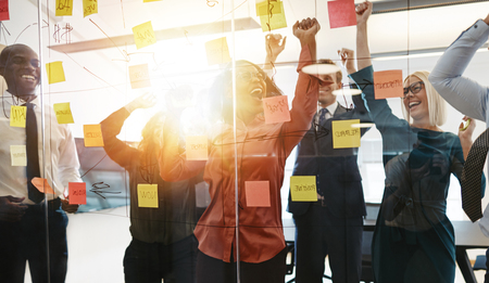 Ecstatic group of diverse businesspeople yelling and jumping up and down while brainstorming with sticky notes on a glass wall in a modern office