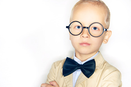 Cute little blonde boy dressed like a professor wearing a suit, bowtie and glasses standing confidently against a white background