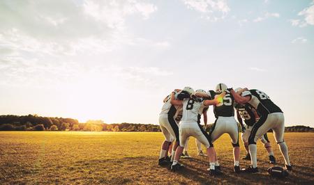 Un gruppo di giovani giocatori di football americano in piedi in un huddle insieme su un campo sportivo nel pomeriggio che discutono prima di una partita