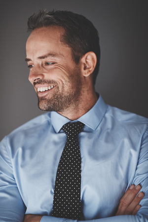 Smiling young businessman wearing a shirt and tie standing against a gray background with his arms crossed