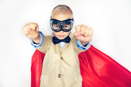 Cute little boy superhero in a suit and bowtie wearing a red cape and goggles pretending to fly while standing against a white background
