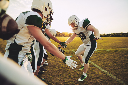 American football player giving his teammates low fives on a sportsfield field after a winning game in the afternoon