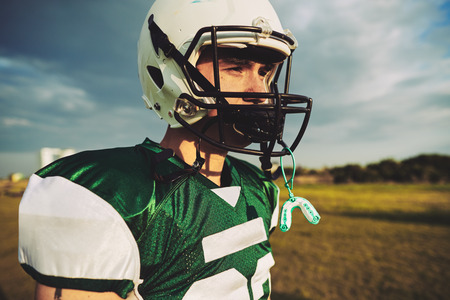 Young American football player taking a break with his mouth guard hanging from his helmet during a team practice session Stock Photo