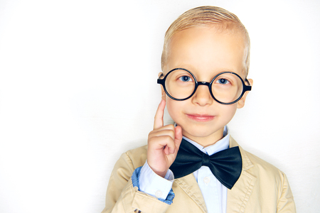 Smiling little blonde boy dressed like a professor wearing a suit, bowtie and glasses pointing in the air against a white background