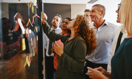 Group of diverse businesspeople strategizing with sticky notes on a glass wall while working together in a modern office Imagens