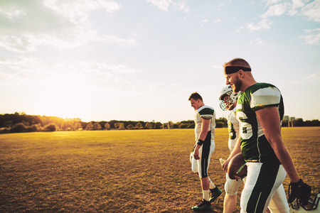 Team of young American football players walking off a sports field together after an afternoon practice session Stock Photo