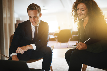 Two diverse young businesspeople smiling while discussing work and going over notes together in a modern office