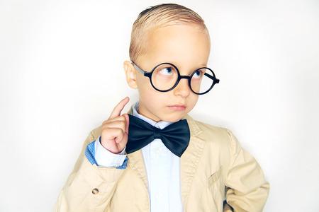 Entzückender kleiner blonder Junge, der einen Anzug, eine Fliege und eine Brille trägt wie ein Professor, der gegen einen weißen Hintergrund zeigt