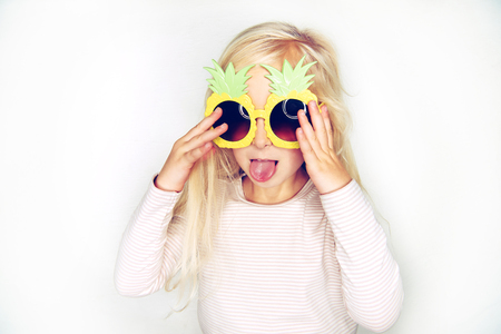 Adorable little girl with long blonde hair wearing funny pineapple sunglasses sticking out her tongue and making a face against a white background