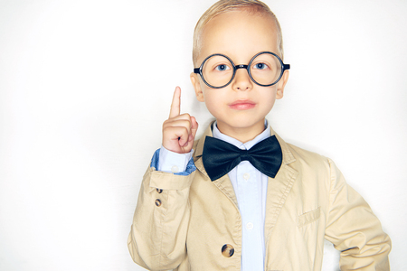 Cute little blonde boy dressed like a professor wearing a suit, bowtie and glasses pointing in the air against a white background