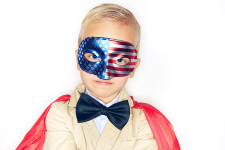 Adorable little boy superhero wearing a suit, bowtie, red cape and a stars and stripes mask looking fearless against a white background